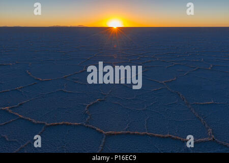 The last sun rays shining on the desert of salt in the Uyuni salt flat at sunset in the Bolivian altiplano (Salar de Uyuni), Bolivia, South America. - Stock Photo