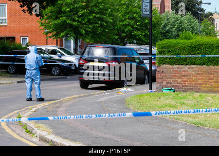 London, England. 11th June 2018. The morning after another teenager is stabbed in London, a forensic officer checks the crime scene for clues within an area cordoned off by the Police. This stabbing happened just a short time after a man was stabbed a few miles away in Northolt. ©Tim Ring/Alamy Live News Stock Photo