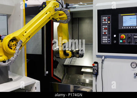 CNC lathe machine and robot used for automation of loading and unloading operations. Selective focus. - Stock Photo