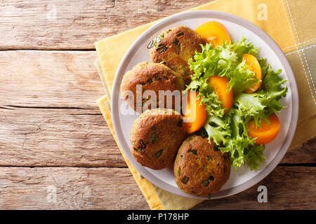 Homemade pancakes made of tuna with spices are served with fresh vegetable salad close-up on a plate on the table. horizontal top view from above - Stock Photo