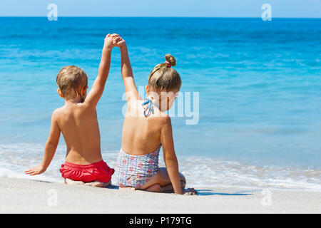 Happy kids have fun in sea surf on sand beach.  Children sit in water pool with hands up. Travel lifestyle, swimming activities in family holiday - Stock Photo