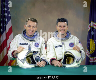 The original Gemini 9 prime crew, astronauts Elliot M. See Jr. (left), command pilot, and Charles A. Bassett II, pilot, in space suits with their helmets on the table in front of them. On February 28, 1966 the prime crew for the Gemini 9 mission were killed when their twin seat T-38 trainer jet aircraft crashed into a building in which the Gemini spacecraft were being manufactured. They were on final approach to Lambert-Saint Louis Municipal Airport when bad weather conditions hampered pilot See's ability to make a good visual contact with the runway. Noticing the building at the last second a - Stock Photo