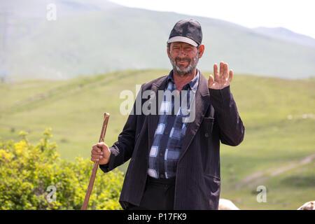 Tatev, Armenia - Jun 2, 2018: A friendly Armenian sheep herder waving hello on a sunny day. - Stock Photo