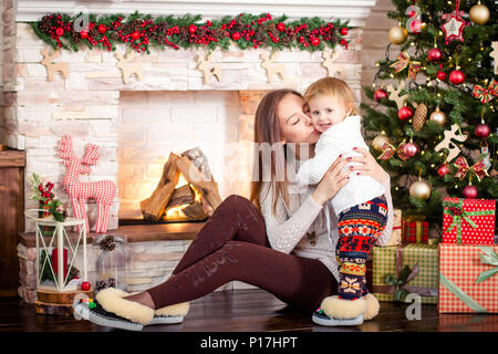 Young mother sitting with little daughter near decorated fireplace and christmas tree. - Stock Photo