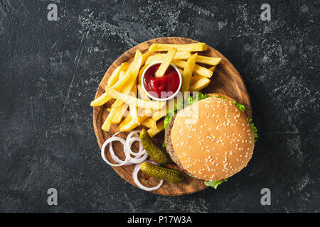 Burger, hamburger or cheeseburger served with french fries, pickles and onion on wooden board. Top view. Fast food concept - Stock Photo
