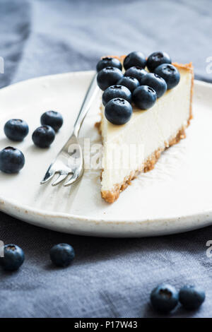 Slice of classical new york cheesecake topped with fresh blueberries. Closeup view, selective focus - Stock Photo