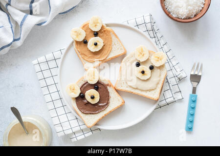Breakfast toasts with nut butter and banana with cute funny animal face. Kids food, breakfast for kids or school lunch. Top view - Stock Photo