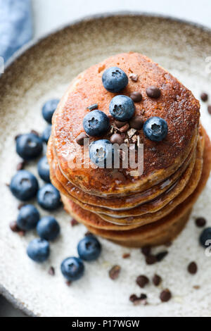 Buckwheat pancakes with cocoa nibs and blueberries. Closeup view, selective focus - Stock Photo