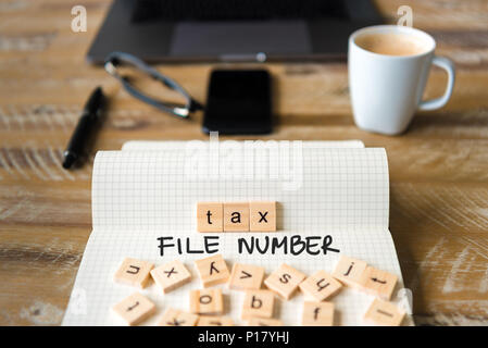 Closeup on notebook over vintage desk surface, front focus on wooden blocks with letters making Tax File Number TFN text. - Stock Photo