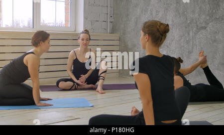 Group smiling women before training talking and stretching in yoga class - Stock Photo