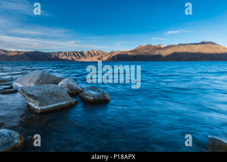 Pangong lake view of blue water with arid mountain with sunlight landscape. - Stock Photo