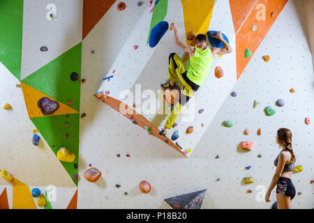 Rock climbers in climbing gym. Young man climbing bouldering problem (route), girl climber watching him. - Stock Photo