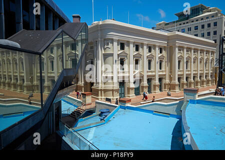 Wellington Town Hall, water feature, and reflection in Michael Fowler Centre, Civic Square, Wellington, North Island, New Zealand - Stock Photo