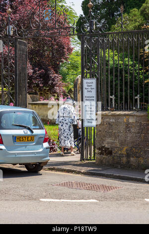 An Elderly lady arrives for a wedding at the church of St Mary the Virgin and St Mary Magdalen in Tetbury. She pushes and elderly man in a wheelchair, Gloucestershire UK - Stock Photo