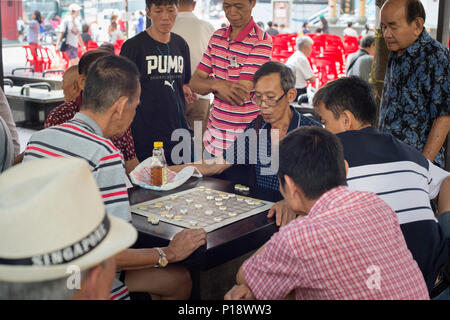 SINGAPORE - FEB 17, 2017: Men play checkers on a street of Chinatown district in Singapore. Ethnic Chinese began settling in Chinatown circa 1820 - Stock Photo