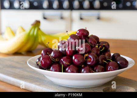 Detailed interior close up of white ceramic bowl piled high with shiny, red cherries. Fruit bowl on UK kitchen table. Food, fruit photography. - Stock Photo