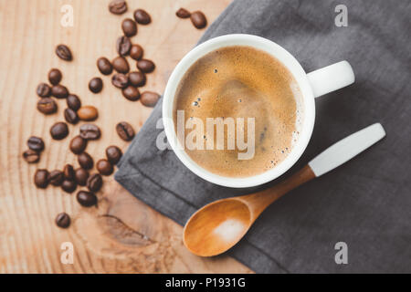 Cup of steaming coffee cup with a wooden spoon and roasted coffee beans on gray textile . Top view, flat lay - Stock Photo