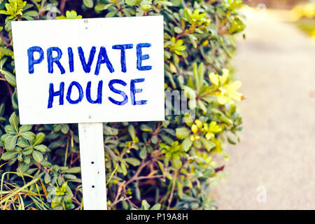 Daylight view to private house wood sign. Green bushes and road on background. Protaras, Cyprus - Stock Photo