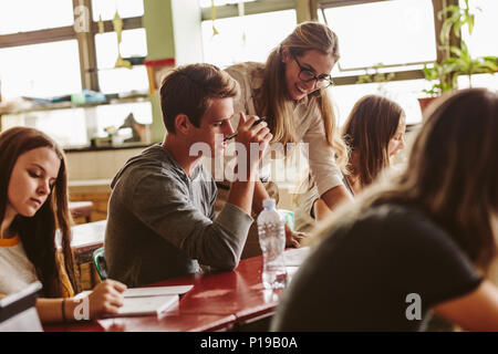 Female professor talking to one of students at lecture and looking at his notebook. Teacher during her class with students sitting at the desks. - Stock Photo