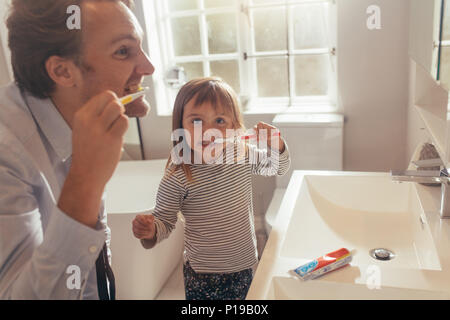 Father and daughter brushing teeth standing in bathroom. Man teaching his daughter how to brush teeth. - Stock Photo