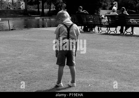sad young boy standing alone in shorts black and white photo - Stock Photo
