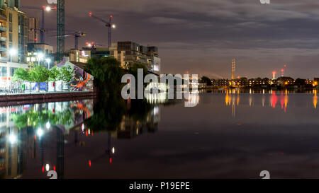 Dublin, Ireland - September 17, 2016: Modern apartment and office buildings are reflected in the Grand Canal Dock alongside old warehouses and industr - Stock Photo
