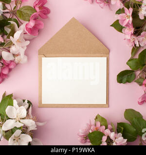 Festive flower apple tree composition and invitation on craft envelope on the pastel pink background. Overhead view - Stock Photo