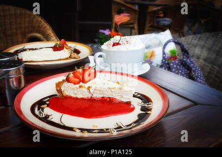Cheesecake with fresh strawberries on plate and a cup of Viennese coffee with whipped cream on a brown wooden table in a summer outdoor cafe. Relaxing cozy old town atmosphere. offee break, dessert. - Stock Photo