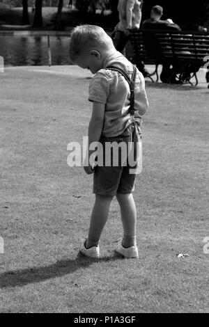 young boy standing alone in shorts black and white photo - Stock Photo