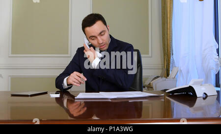 Young disabled businessman, saffered from Parkinson s disease, sitting in an office chair, doing paperwork and answering phone calls - Stock Photo