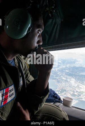 Petty Officer 3rd Class Corbin Warren, crew member aboard an HC-130 Hercules airplane from Air Station Clearwater, keeps a trained eye for anyone in distress as he communicates with his aircrew Thursday, Oct. 6, 2016. Warren and his crew launched to transport personnel and supplies to support post Hurricane Matthew relief efforts in Great Inagua, Bahamas, and various affected areas the storm passed. U.S. Coast Guard photo by Petty Officer 1st Class Michael De Nyse - Stock Photo