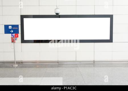 One big horizontal / landscape orientation blank billboard in public transport with blurred passenger background