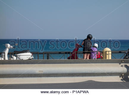 Europe, Greece, 2018: View Of Mother With Daughter And Moped At Seaside - Stock Photo