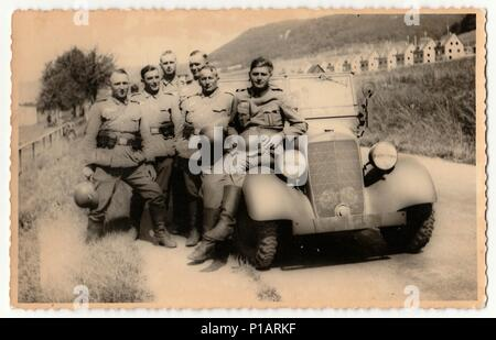 GERMANY - CIRCA 1940s: Vintage photo shows German Nazi soldiers stand at convertible. - Stock Photo
