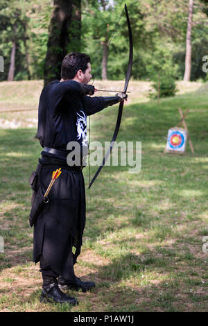 Nis, Serbia - June 10, 2018: Medieval archer with big wooden bow and long arrow in forest. Living history festival. Archery tournament - Stock Photo