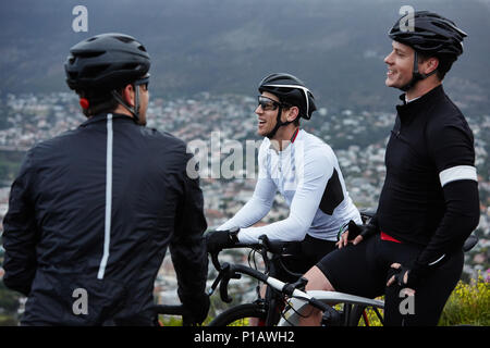 Male cyclist friends taking a break, talking - Stock Photo