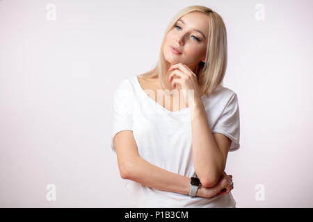 pleasant blond-haired female touching her chin and thinking about boyfriend - Stock Photo