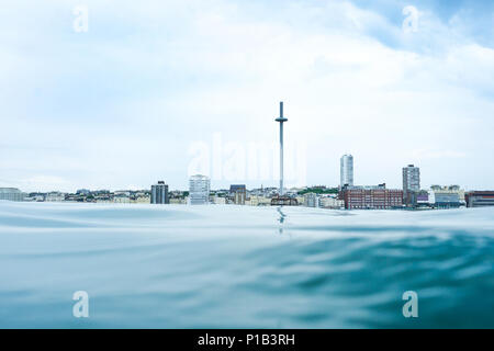 Brighton seafront view point from the sea, at the bottom is a calm glass like flat sea in the middle is the skyline of Brighton, UK, with the I360 vie - Stock Photo