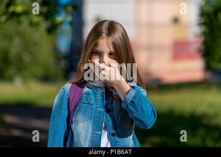 A little blond girl covered her mouth with her hand. Emotions of fear of fear. Summer outdoors in fresh air. The teenager looks away in surprise. At the break after school. - Stock Photo