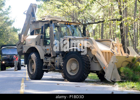 Soldiers from the 122nd Engineer Battalion, South Carolina National Guard, clear debris from a roadway near Mcclellanville, South Carolina in the aftermath of Hurricane Matthew, Oct. 9, 2016. Over 2,000 South Carolina National Guard Soldiers and Airmen have been activated since Oct. 4, 2016. Their primary mission is supporting state and county emergency management agencies and local first responders with coastal evacuations and any services or resources needed to assist the citizens of South Carolina after Governor Nikki Haley declared a State of Emergency. Hurricane Matthew peaked as a Catego - Stock Photo