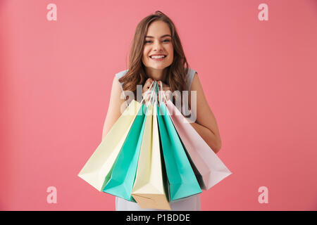 Image of cheerful young woman standing isolated over pink background holding shopping bags. Looking camera. - Stock Photo
