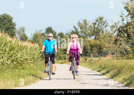 Active senior couple enjoying retirement while riding bicycles in the park - Stock Photo