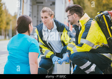 Emergency medics talking to injured woman - Stock Photo