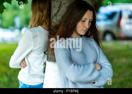 Two girlfriends in the summer in a park in nature. Offended each other. Friends quarreled. Negative among the girls. Problems in the relationship. Dissatisfaction with each other. Stand near a tree. - Stock Photo