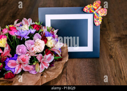 beautiful bouquet with different colors and photo frame on a wooden background. Colorful bouquet of different fresh flowers, close-up - Stock Photo