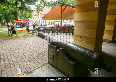 VINKOVCI, CROATIA - MAY 14, 2018 : People passing by an old metal cannon which is set outside of the city museum building in Vinkovci, Croatia. - Stock Photo