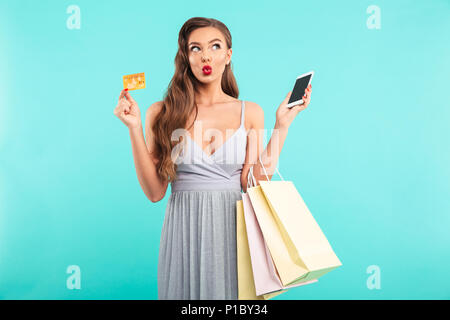 Charming shopaholic woman holding shopping bags and paying with smartphone and credit card isolated over blue background - Stock Photo