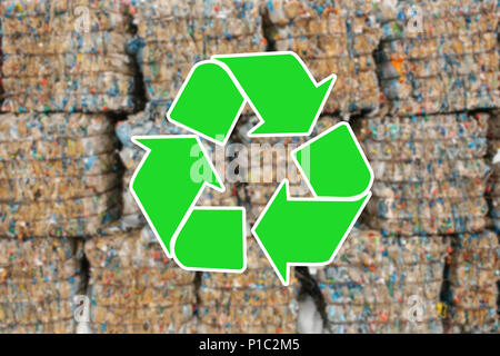 Sign recycling waste. The pile of waste is blurred in the background - Stock Photo