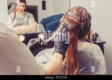 Female stylist applying a dye to the clients hair at beauty salon - Stock Photo