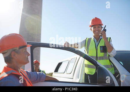 Portrait smiling, confident female engineer using walkie-talkie at truck - Stock Photo